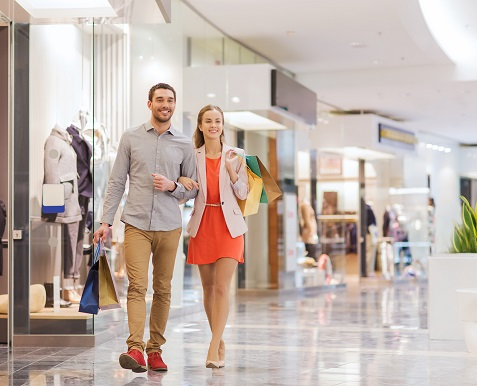 sale, consumerism and people concept - happy young couple with s